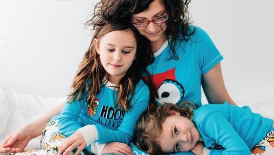 Mother and two daughters wearing owl themed pyjamas from Lazy One®
